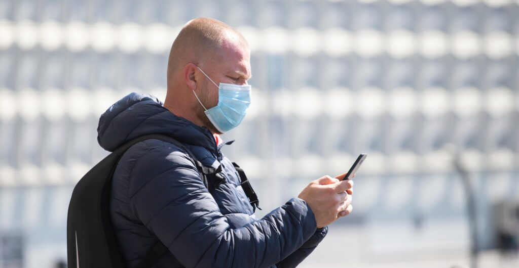 Tourist man in a medical surgical mask in the city.
