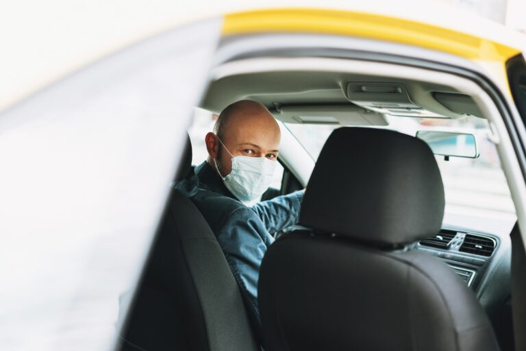 Bald man taxi driver in medical face mask inside yellow car