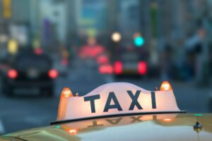 Closeup of a taxi sign on top of a taxi cab in the city at night.
