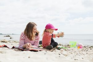 Woman playing with daughter at beach