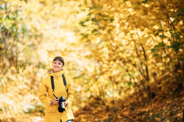 Aurlandsfjellet, Norway. Young Woman Tourist Photographer Walking With Photo Camera In Autumn Yellow
