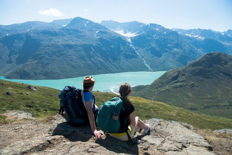 couple of hikers resting and looking at Besseggen ridge over Gjende lake in Jotunheimen National