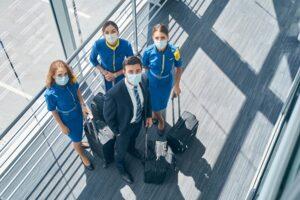 Four flight attendants in masks looking up