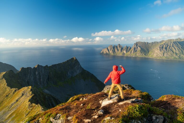Man with arms spread in celebration on top of mountain, Senja Island, Troms